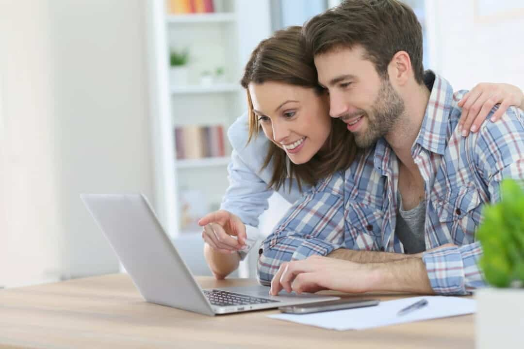A couple calculating in front of the laptop