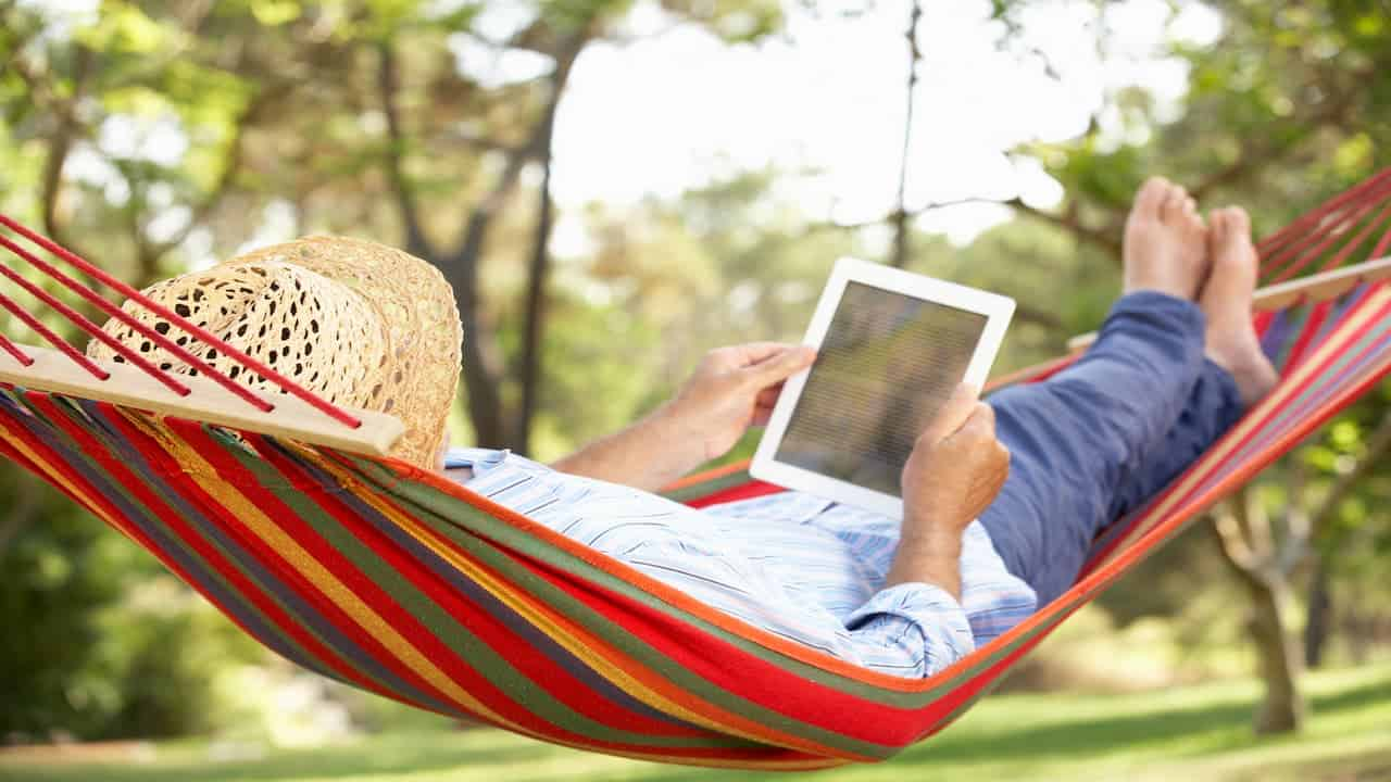A person in a hammock holding a notebook