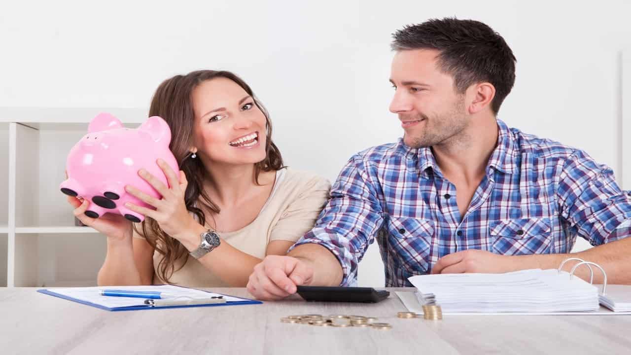 A smiling couple counting their savings