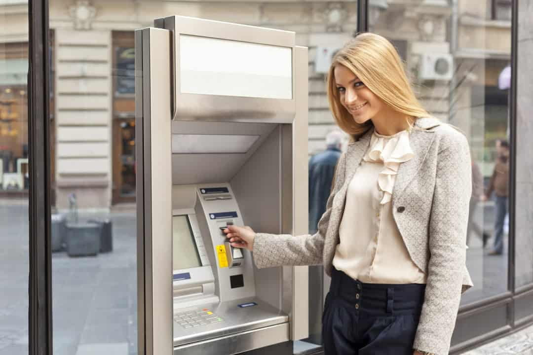 a young blonde woman using ATM machine