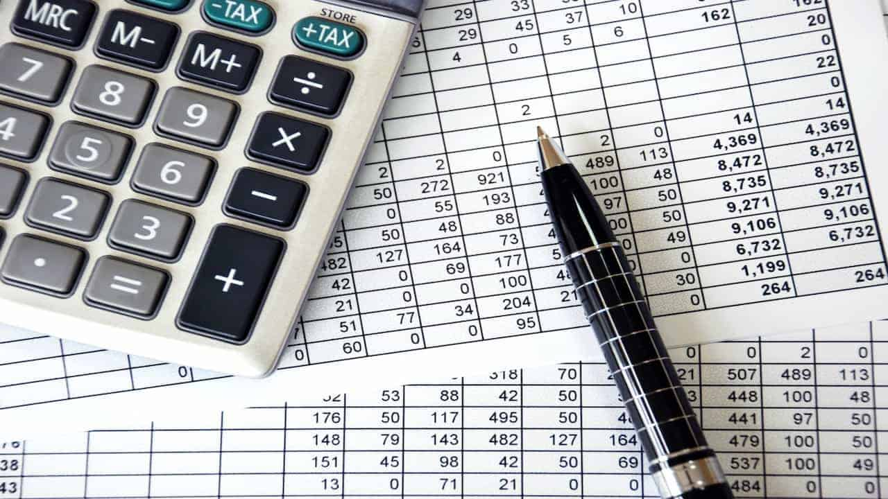Accounting charts, a calculator and a pen