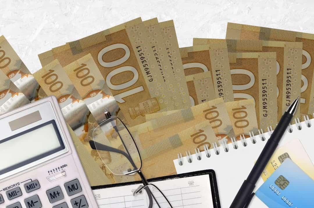 Canadian dollars, calculator, reading glasses and notes