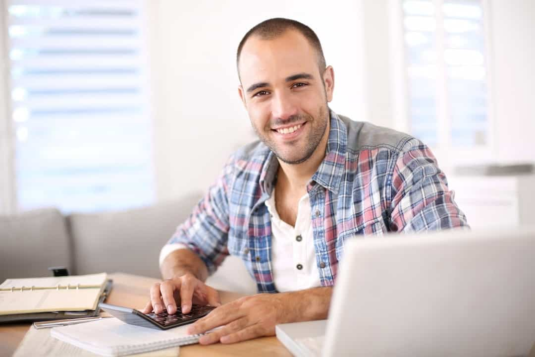 a smiling young man using calculator and a laptop