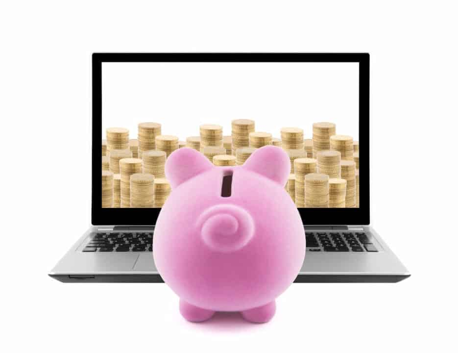 Piggy bank in front of the laptop with coin stacks on the screen