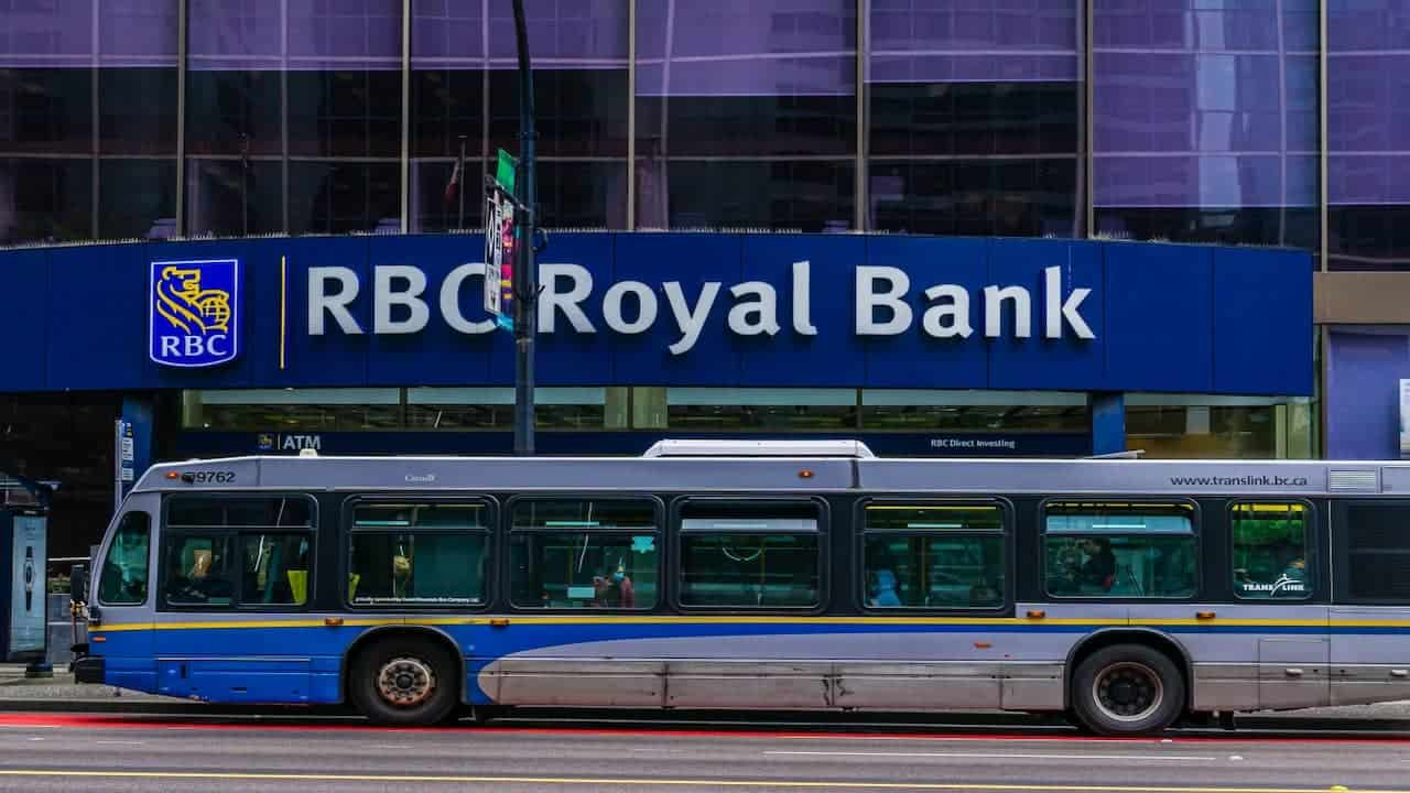 a bus with a RBC building in the background