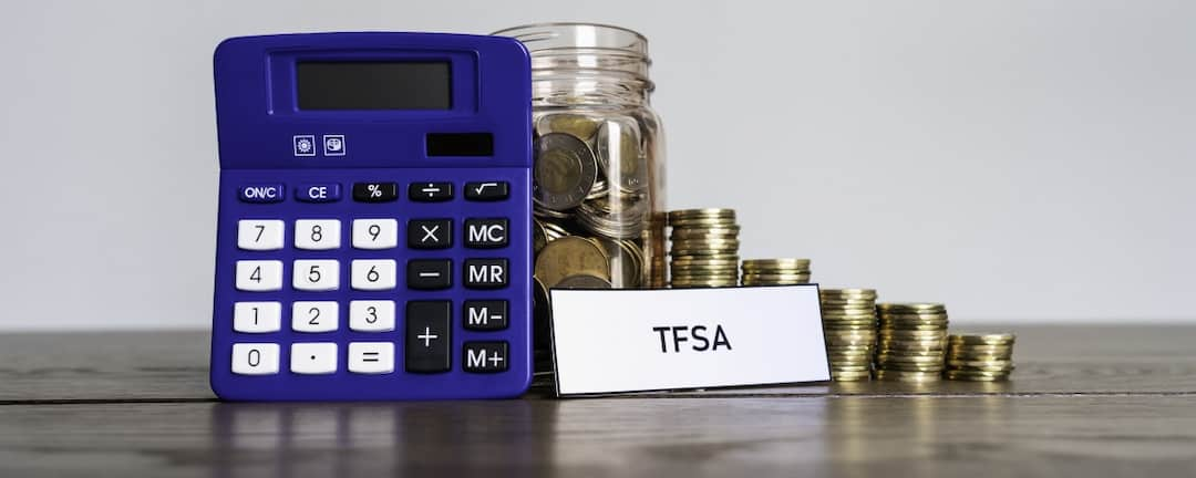 Calculator, TFSA tag and stack of coins