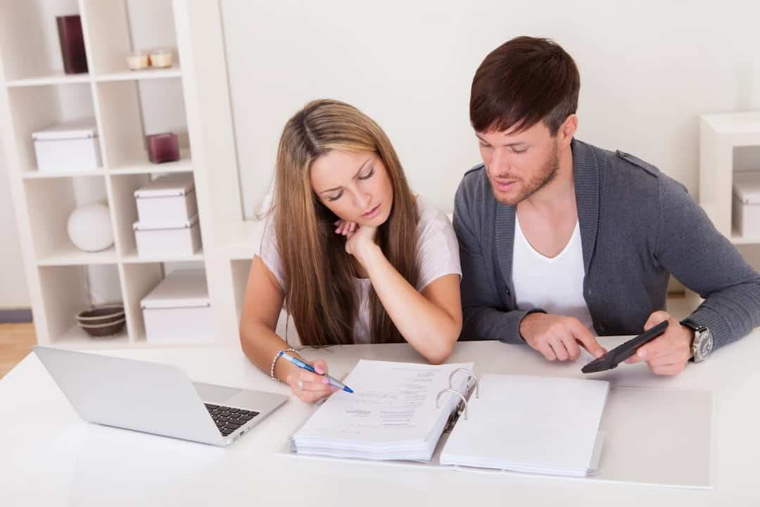 a young couple sitting at the table and calculating