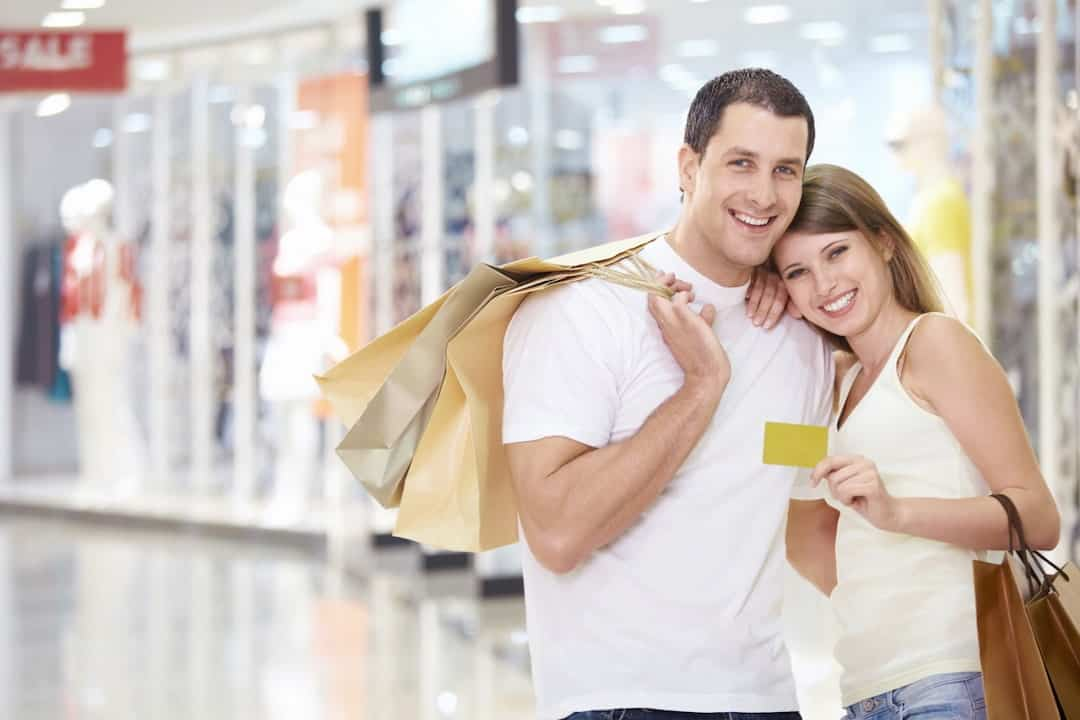 a smiling couple with a credit card and shopping bags