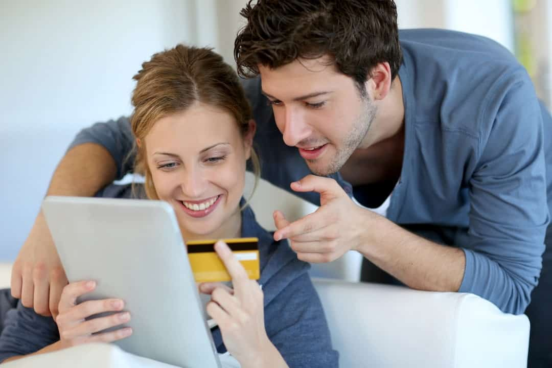 a smiling couple using tablet and credit card