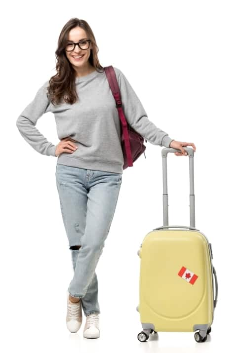 a young smiling woman with backpack and suitcase