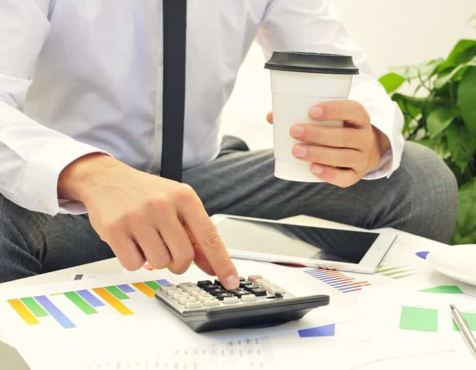 a man using a calculator with a cup of coffee in one hand