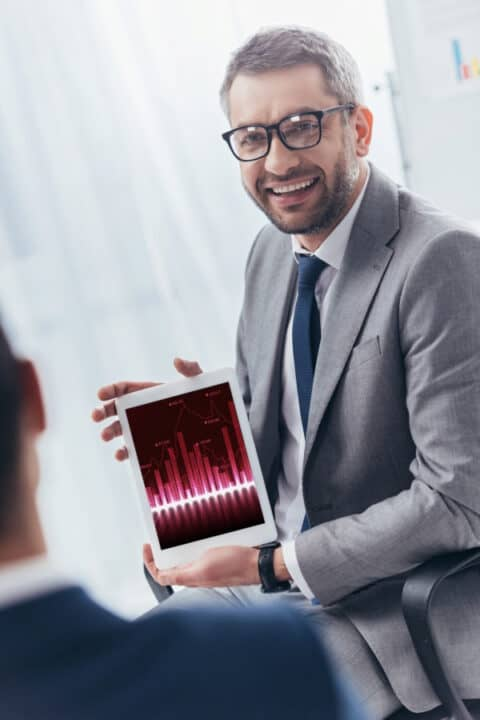a man holding tablet with graph on the display