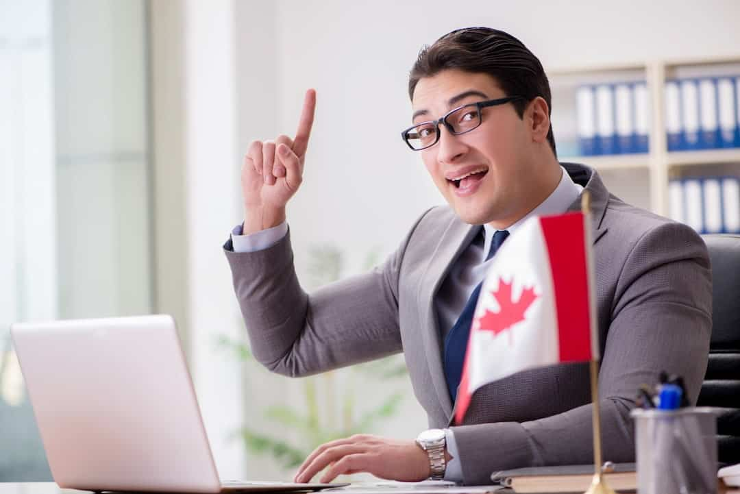 a man in the office with a Canadian flag on the table