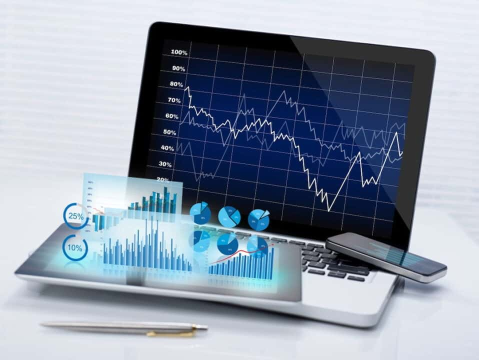 stock charts and graphs, a laptop and a cellphone