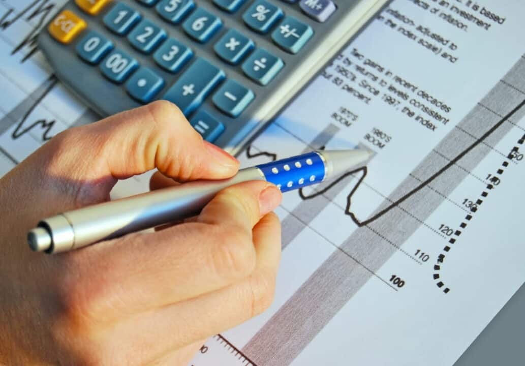a hand holding a pen and making notes on the graph