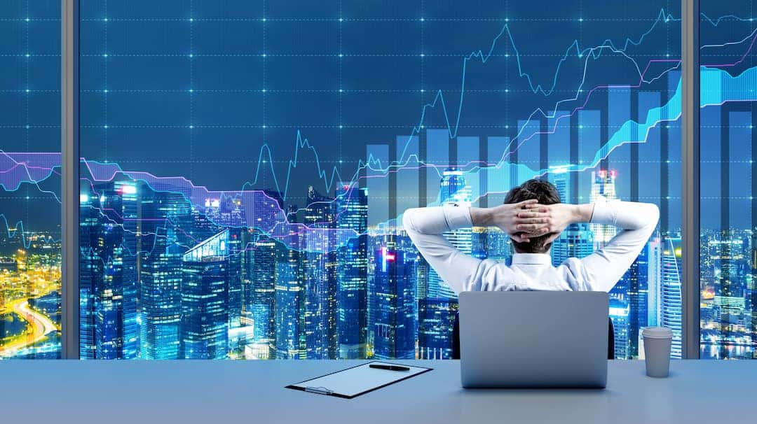 a trader looking at the stocks graphs on the big display
