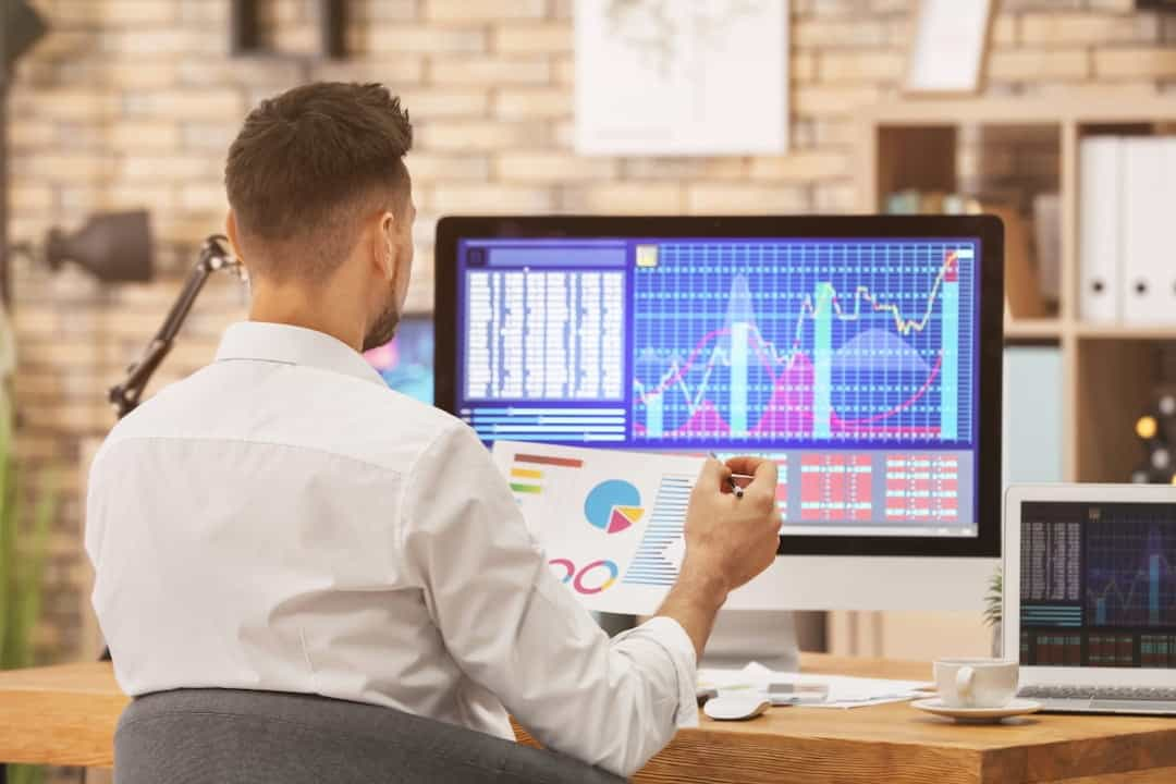 a man in front of the computer monitor trading with stocks