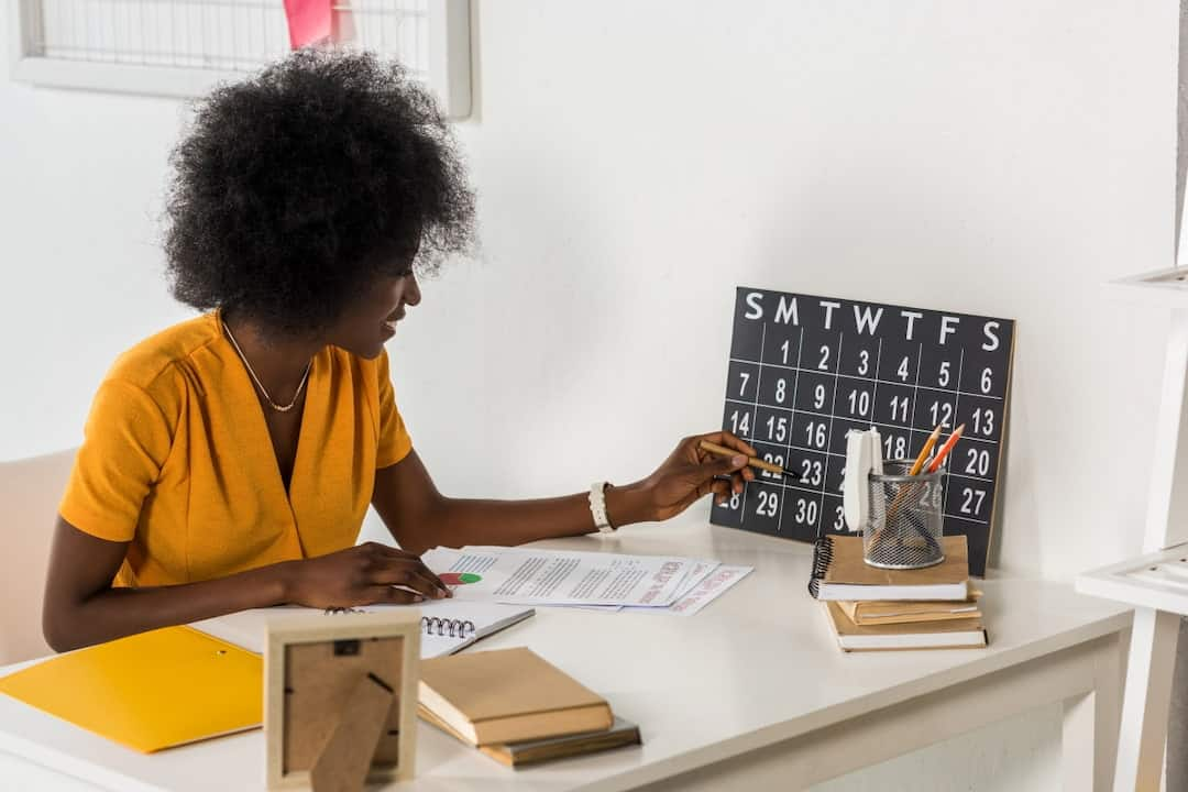 a woman in yellow dress checking the calendar in her office
