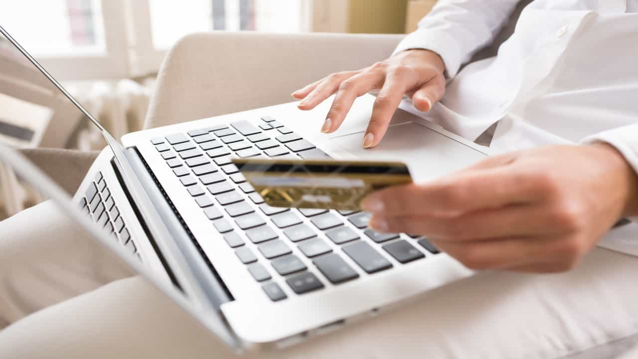 a person holding a credit card and using laptop