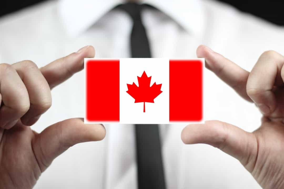 a man holding credit card with Canadian flag between his fingers