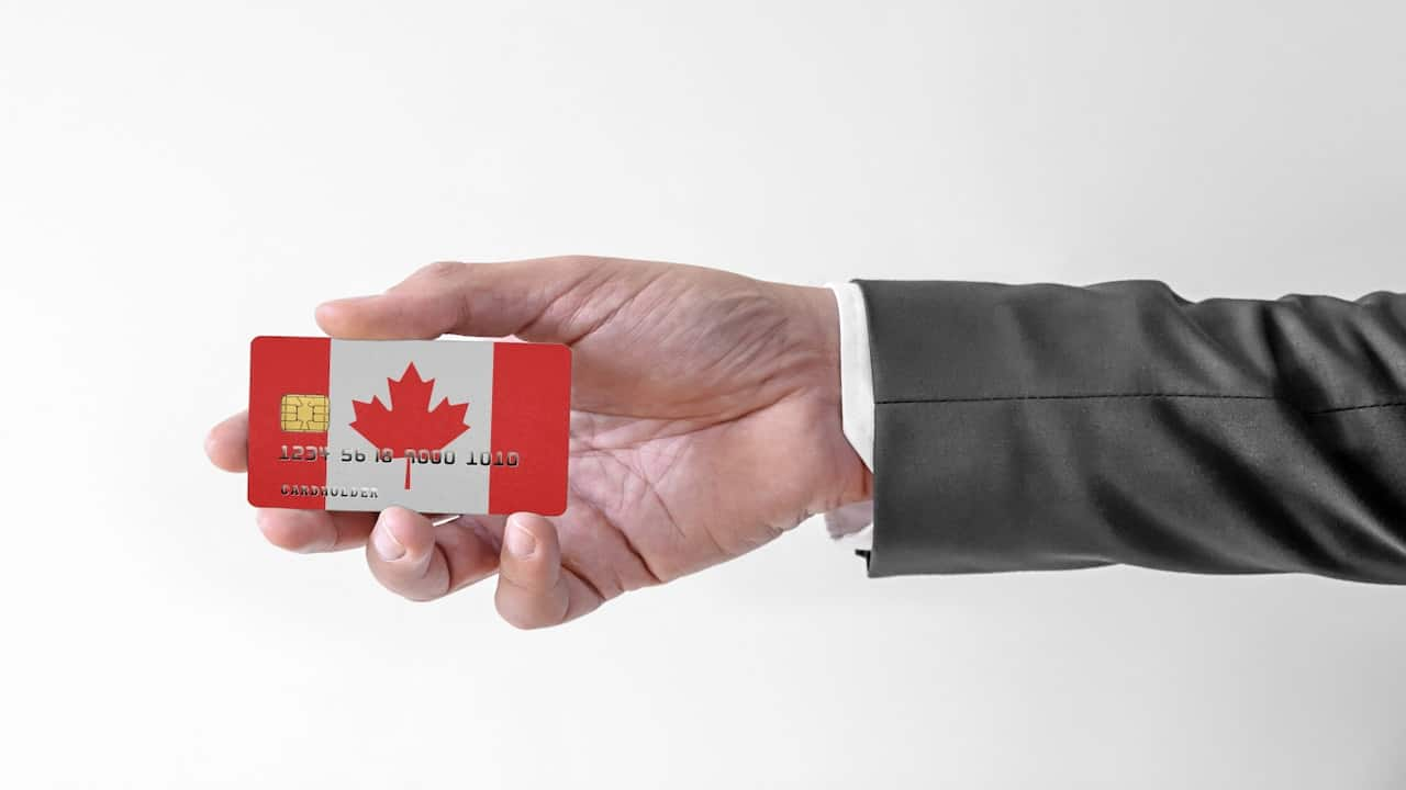 plastic bank card with Canadian flag in a person's hand