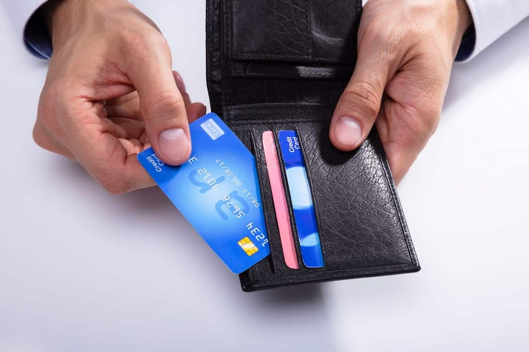a man holding a wallet with credit cards in his hands