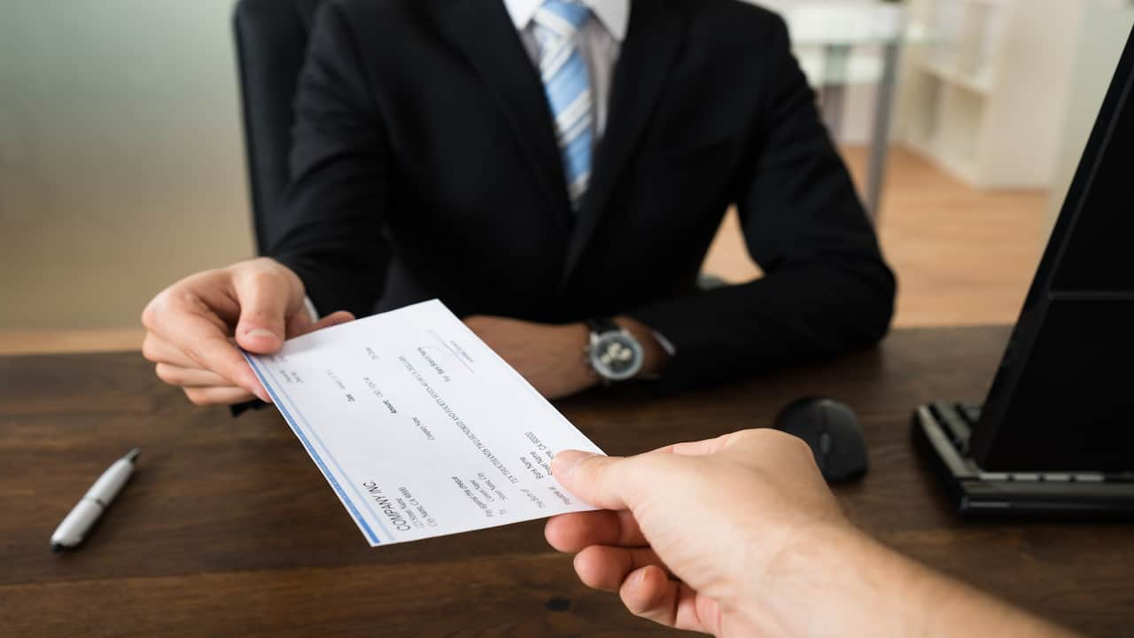 a person giving a cheque to other person