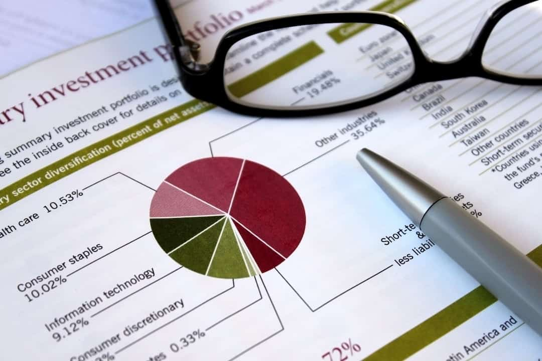 investment portfolio, glasses and a pen