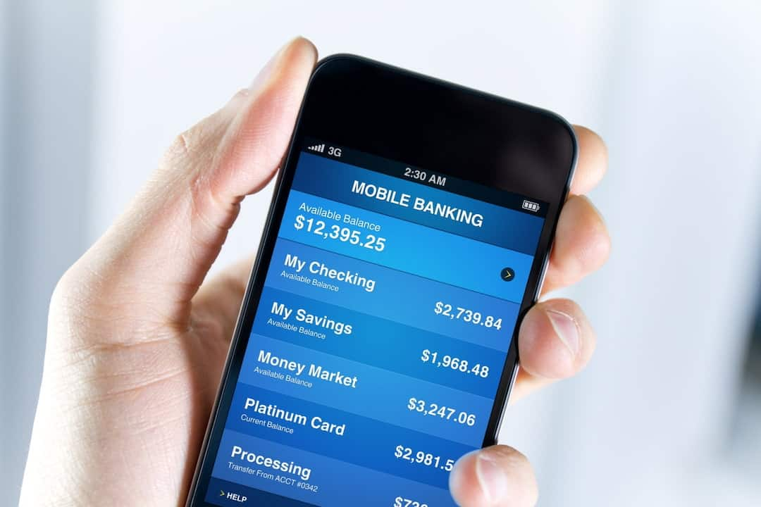 a hand holding mobile phone with digital banking features displayed