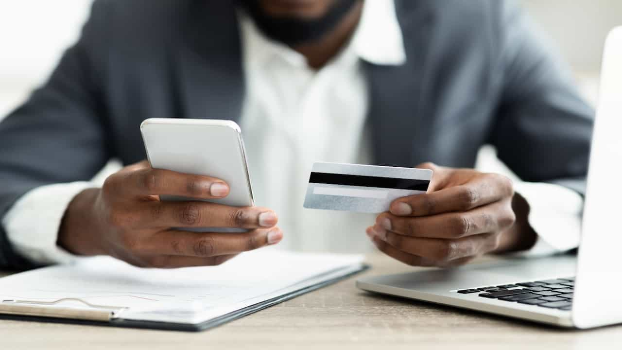 a man with mobile phone and credit card in his hands sitting at the table