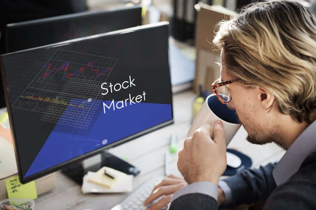 a man in front of the monitor with stock trading platform displayed