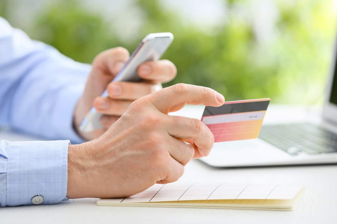 a man holding a credit card and a cellphone