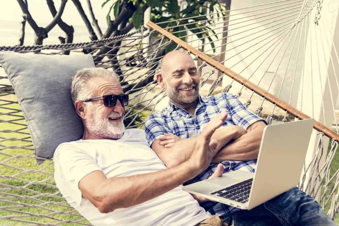 two men looking at the laptop and laughing in a hammock